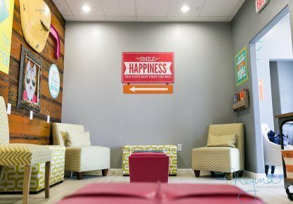 Route 32 Dental kids play room seating area view of wall decoration with animated character on wood planks wall on the left and an office sign: Smile is Happiness on the facing wall