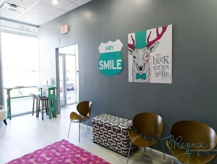 Route 32 Dental kids play room seating area view of wall decoration with animated character an office sign: Smile HWY and The buck stops here