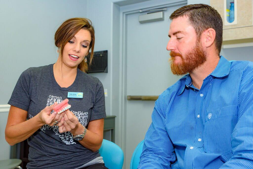 Route 32 Dental team member holding a gums and teeth form while in consultation with an adult bearded male patient