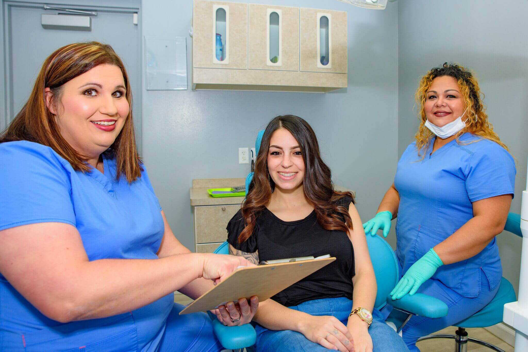Three team members inside one of Route 32 Dental treatment rooms