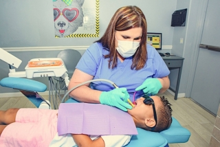 Route 32 Dental team member wearing a mouth and nose mask is working with suction tools cleaning inside the mouth of a young boy patient lying on the dentist treatment chair wearing protective dark glasses