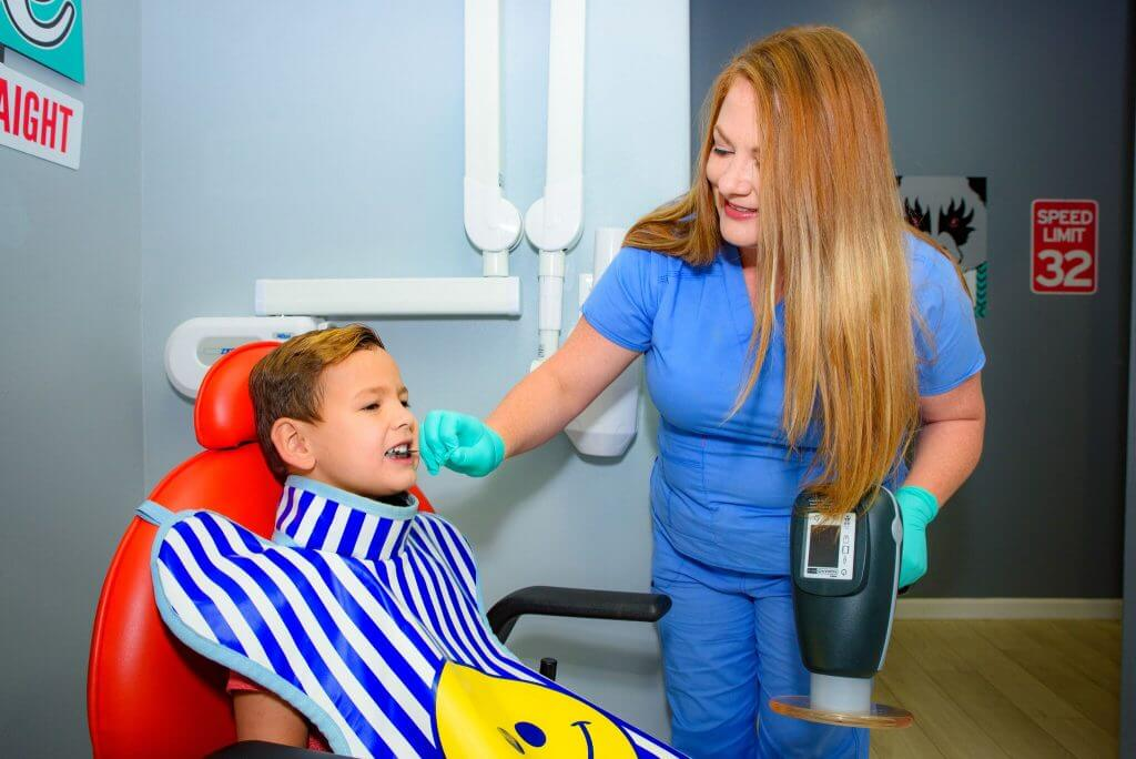 Route 32 Dental team member in blue uniform and green exam gloves holding an X-Ray machine in one hand, while positioning the X-Ray film with the other hand  in the mouth of a young patient who is wearing the protective X-Ray apron with blue stripes and a smiley face print, and is sitting on a red dentist chair