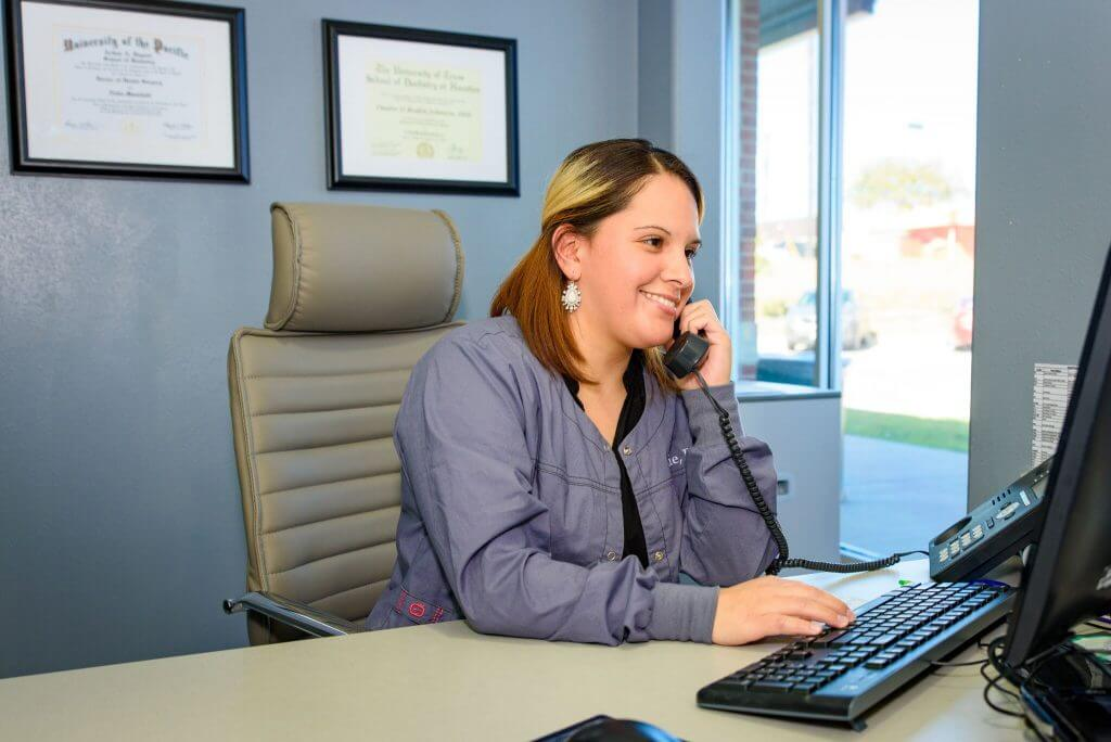 Route 32 Dental office team member smiling while sitting in the office, talking on the phone and typing on the computer