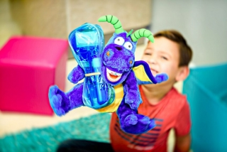 A happy smiling young patient showing off his special promotion gift package bundled with a happy smiling dragon toy