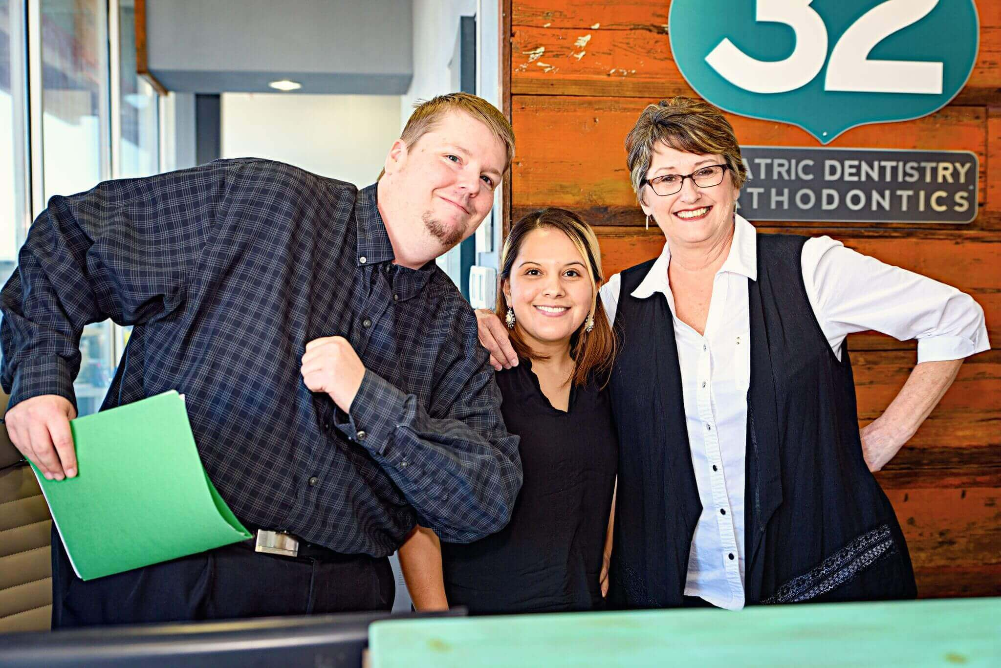 Three office team members of Route 32 Dental in the office reception area
