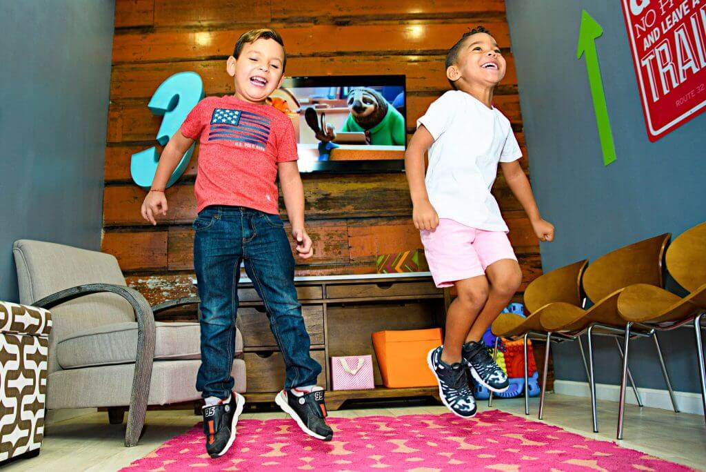 Two young boys patients jumping playfully in the kids play area of Route 32 Dental office