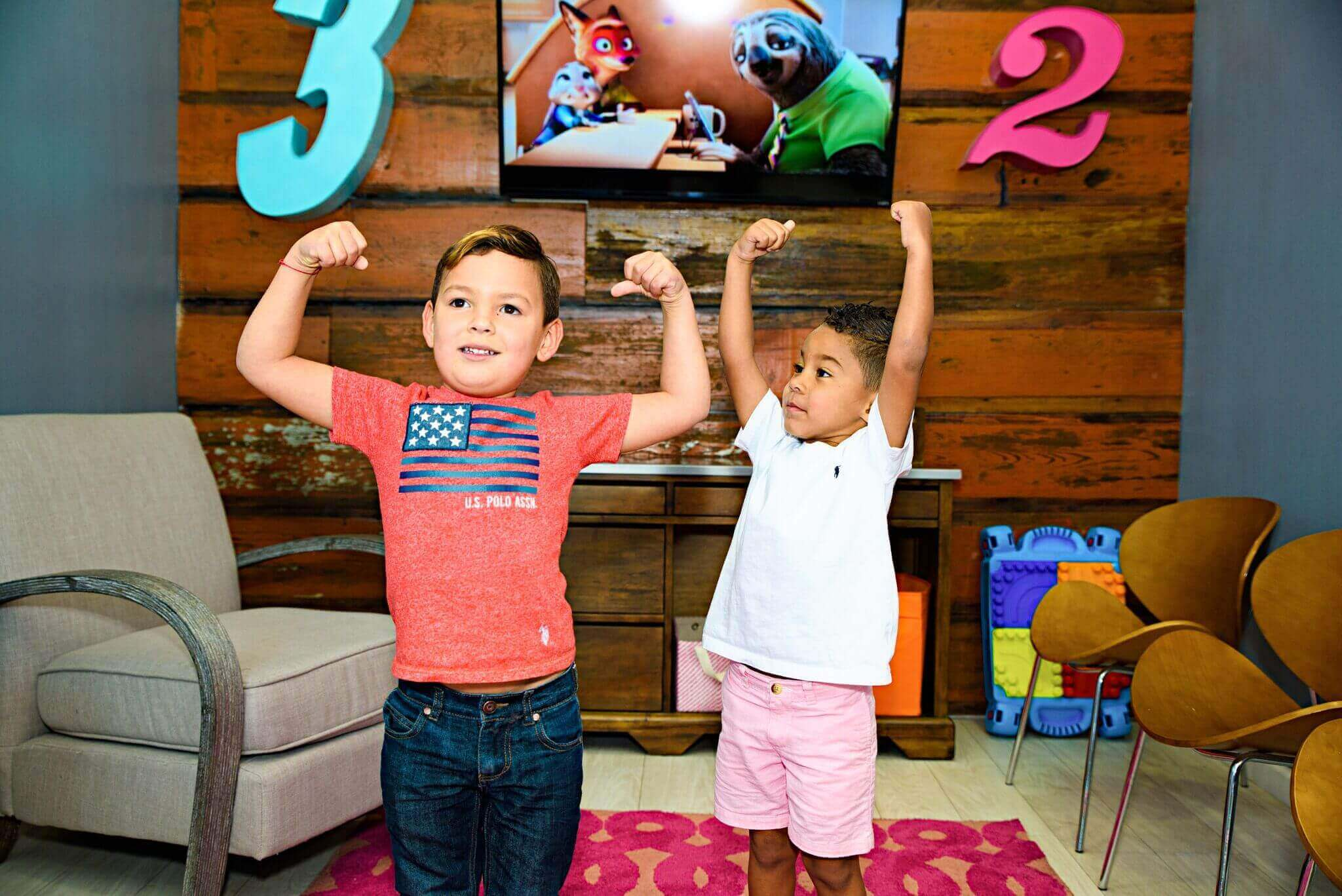 Two young patient boys flexing their hero muscles in the kids play area in Route 32 Dental office